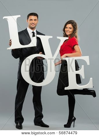 Beautiful smiling couple holding word LOVE made from foam plastic