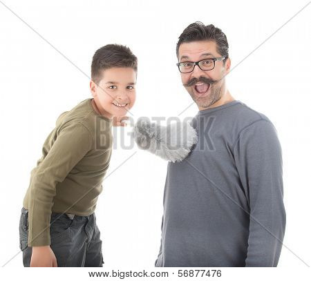 Little boy dusting his father with feather duster isolated on white background