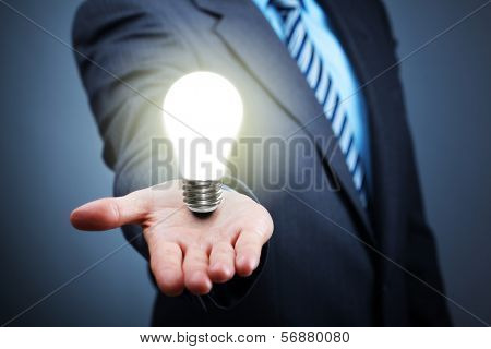 Businessman with illuminated light bulb balancing on his hand concept for idea, innovation and inspiration