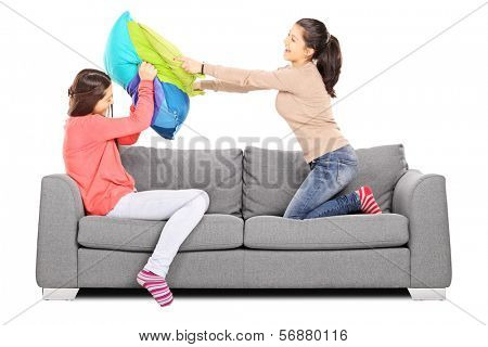 Two young girls having a pillow fight seated on sofa, isolated on white background