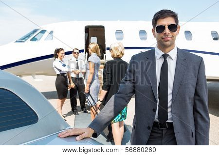 Portrait of confident businessman with airhostess and pilot greeting businesswomen against private jet