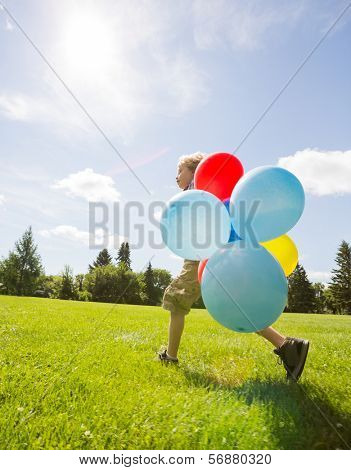 Full length side view of young boy with colorful helium balloons walking in park