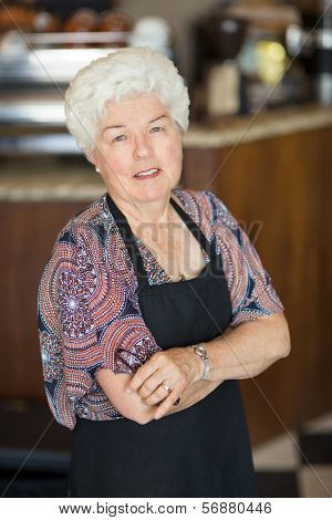 Portrait of confident senior female owner standing arms crossed in coffeeshop