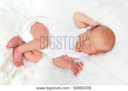 Newborn baby of 11 days old asleep in white clothes and nappy