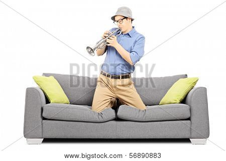 Young man sitting on sofa and blowing on trumpet, isolated on white background