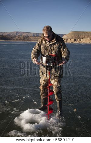 Man In Camo Drilling Hold In Ice With Auger