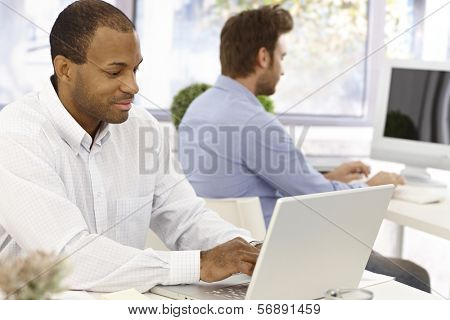 Busy casual office workers sitting at desk, working with computer.