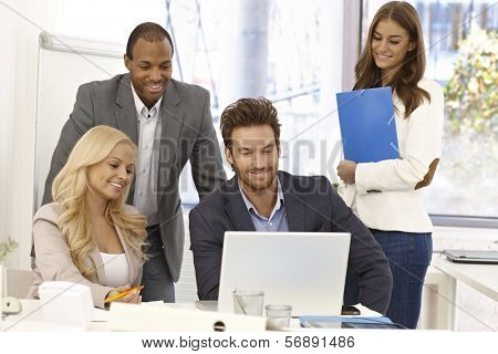 Happy team of young businesspeople working together, using laptop computer, smiling.