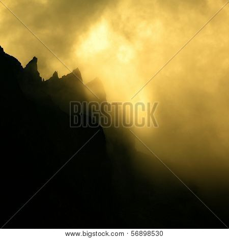 Clouds dramatically glowing over a mountain ridge