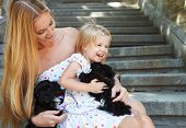 foto of puppies mother dog  - Cute little girl and her mother hugging dog puppies. Friendship and care concept