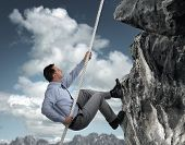 stock photo of crevasse  - Business man climbs a mountain concept for challenge - JPG