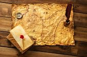 Quill pen, compass and envelope on old map over wooden background