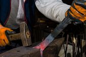 pic of blacksmith shop  - Blacksmith forging hot iron on old envil