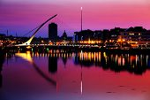 stock photo of nightfall  - North bank of the river Liffey at Dublin City Centre at night with Samuel Beckett Bridge and The Spire as seen from the south bank