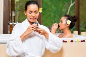 Indonesian Asian women in wellness beauty day spa having aroma therapy bath and drinking herbal tea