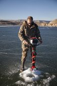 foto of auger  - A man using an ice auger to drill a hole in the ice - JPG
