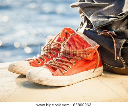 Sneakers And Backpack On Seascape