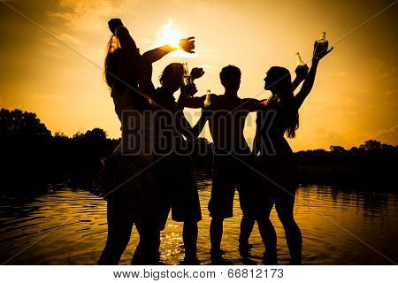 People feeling free in the sunset having a summer party in the water