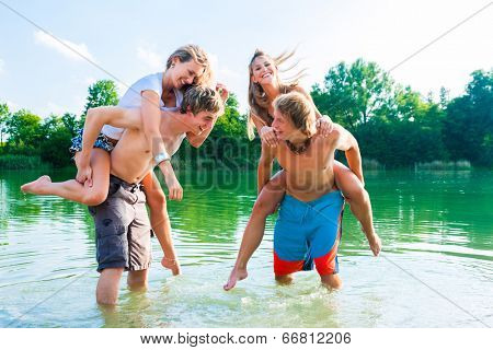 Two couples in love in the water on the beach - having some fun together splashing water at each other
