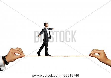 Assured businessman tight rope walking against a white background.