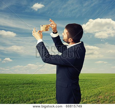 young businessman scrutinizing banknote outdoors