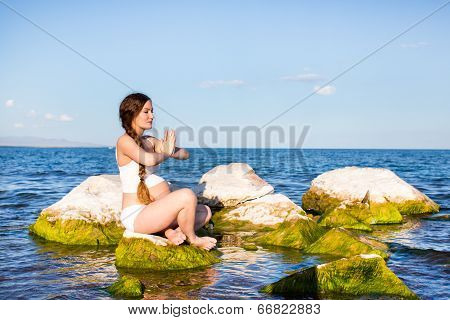 Pregnant Woman In Sports Bra Doing Exercise In Relaxation On Yoga Pose On Sea. The Concept Of Health