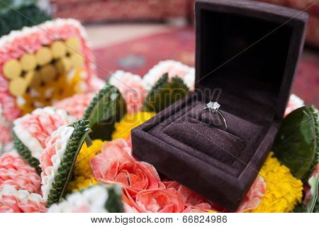 A Diamond Wedding Ring In An Open Box On Traditional Thai Style Garland