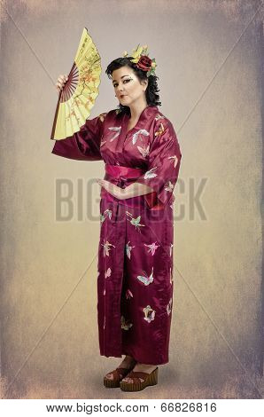 Woman Standing In Traditional National Far Eastern Clothes With Fan