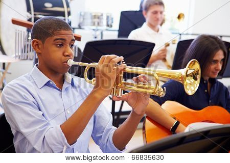 Male Pupil Playing Trumpet In High School Orchestra
