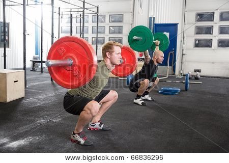 Team trains squats at fitness gym center