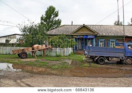 A Cart With One Horse And An Old Soviet Lorry Parked In Front Of The Post Office