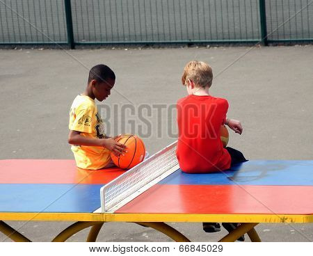 Young boys sit on a table tennis table