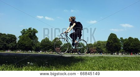 Young woman is cycling in a park