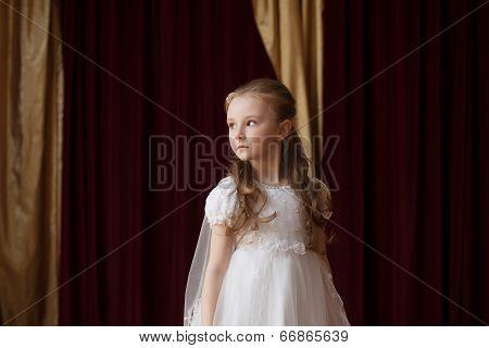 Girlie in white dress posing on curtain backdrop