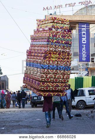 Man Carries Pile Of Foam Mattresses In Merkato Market. Addis Ababa. Ethiopia.