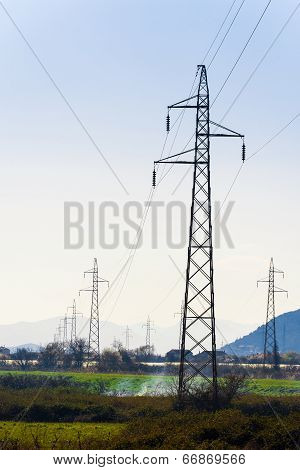 High-voltage Power Lines In The Valley Stretching Into The Distance
