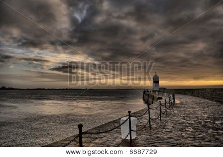 Breakwater wall with old lighthouse with dramatic sky at dusk