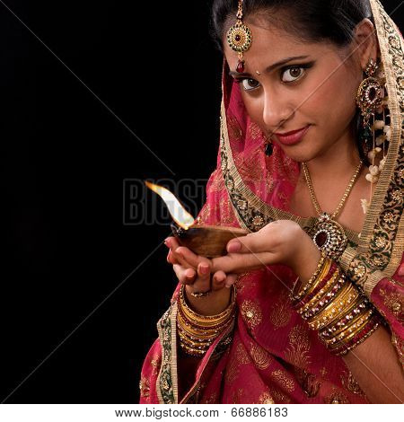 Beautiful Indian girl hands holding diya oil lamp, celebrating diwali festive of lights, traditional sari prayer isolated on black background with copy space on side.
