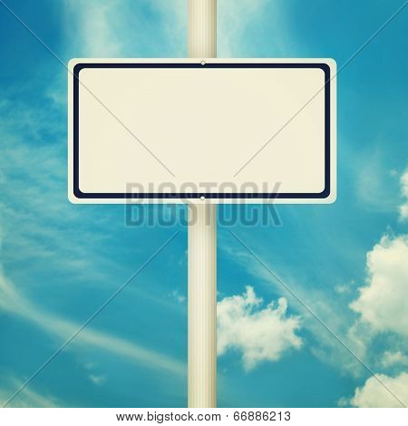 Blank road signs, empty street post, blue sky background in vintage style.