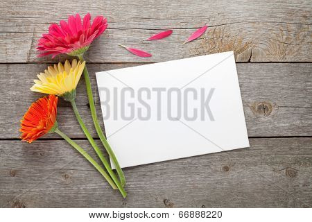 Three colorful gerbera flowers and blank gift card or photo frame on wooden table