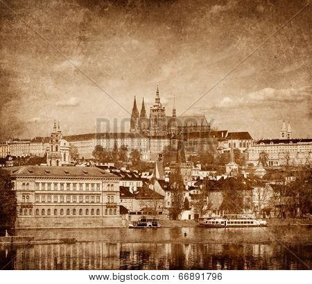 View of Charles bridge over Vltava river and Gradchany (Prague Castle) and St. Vitus Cathedral vintage sepia toned  with grunge texture overlaid