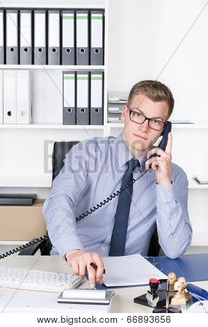 Man Is Phoning And Typing At A Desk Calculator