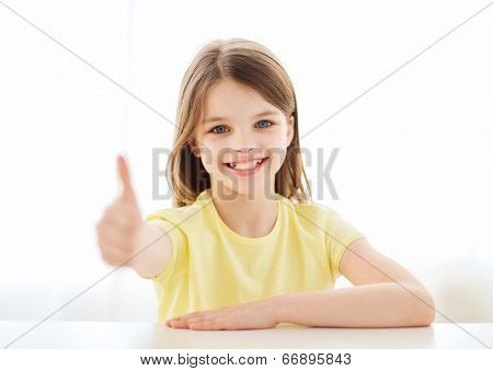 home, education, happiness and people concept - beautiful little girl at home showing thumbs up