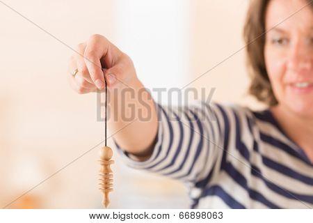Beautiful woman using pendulum