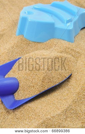 a blue toy shovel and a blue fish-shaped mould on the sand of a beach or a sandpit