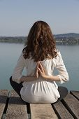 stock photo of namaste  - Young woman is sitting in reverse namaste pose by lake - JPG