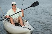pic of canoe boat man  - Man fishing from kayak on a beautiful day at dusk closeup - JPG