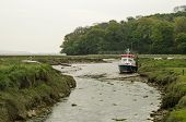 stock photo of marshlands  - A boat moored in a channel through marshland at the River Taf estuary in Laugharne - JPG
