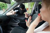 stock photo of mobsters  - Burglar threatens the woman a gun in the car - JPG