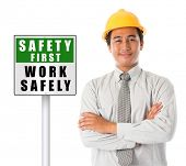 image of workplace safety  - Asian male worker wearing a hardhat smiling and looking at camera - JPG